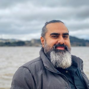 A light brown man with a bushy silver and black beard down to his collarbone. His salt and pepper hair is pulled back in a ponytail. He is smiling while wearing a grey jacket standing in front of a body of water with grey clouds and land in the distance.
