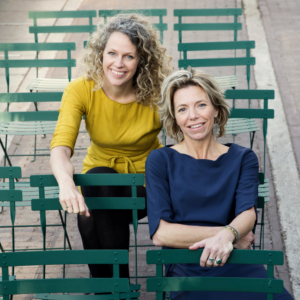 Two white women are sitting near each other in green chairs. The woman on the left has wavy light brown and blond hair, wearing a mustard yellow blouse and black pants. The woman on the right has chin length straight light brown and blonde hair, wearing a dark blue blouse.