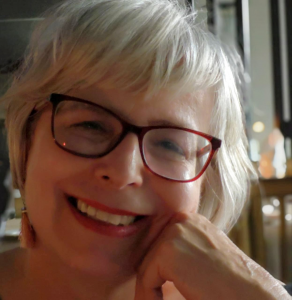 Headshot of a white woman with white hair and red framed glasses. She is smiling with her chin resting on her knuckles