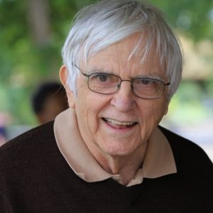 An older white man with wire frame glasses. He has short white hair and is wearing a black sweater with a taupe shirt color sticking over.
